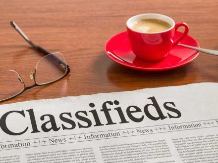 A newspaper on a wooden desk - Classifieds