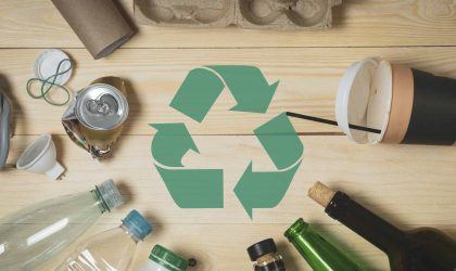 household garbage top view on wooden background, coffee Cup, empty bottles, glass and plastic, spoiled energy saving lamp, green recycling sign in the middle