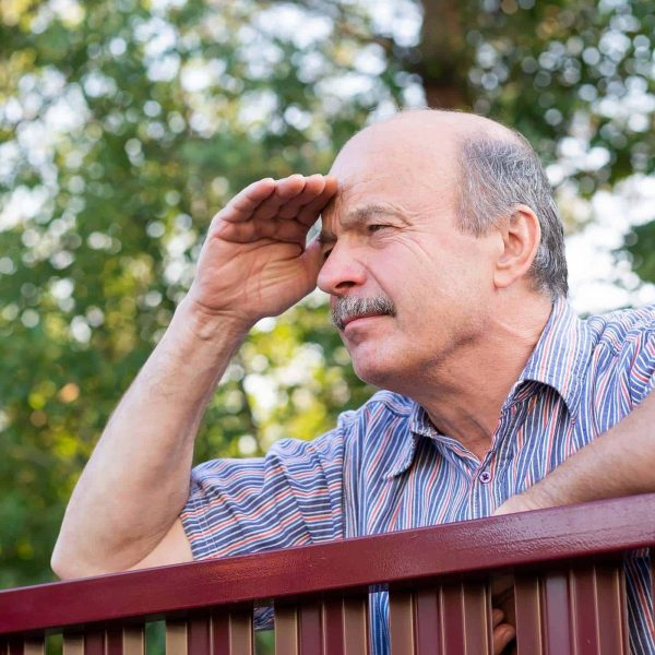 Mature caucasian man carefully watching over the fence. Concept of curious neighbors and private life