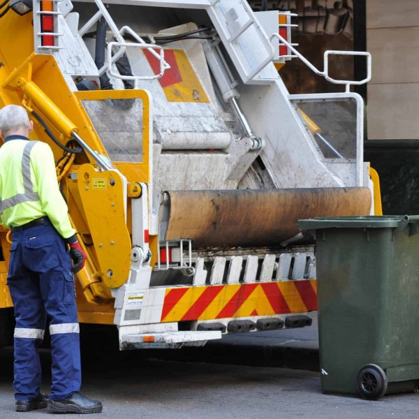 A garbage truck driver working - emptying rubbish into his truck.