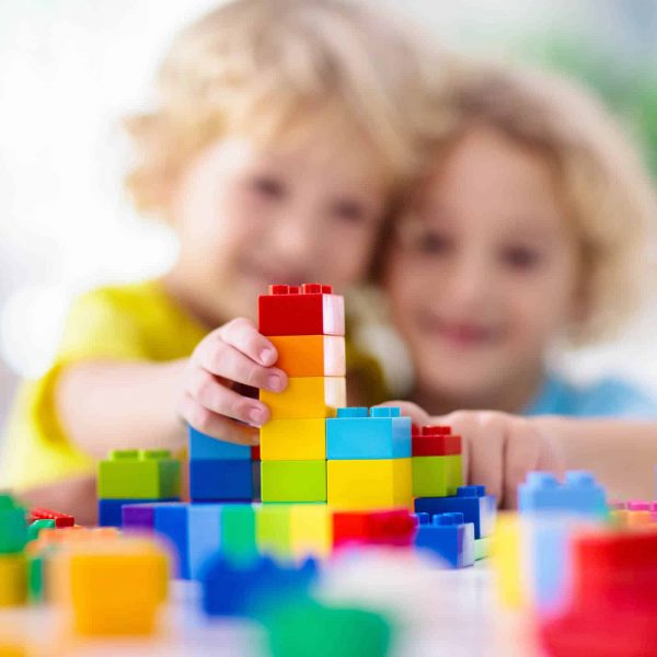 Wynyard Childcare - Kids play with colorful blocks. Little boy building tower at home or day care. Educational toy for young child. Construction creative game for baby or toddler kid. Mess in kindergarten playroom.